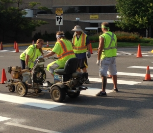 Road being striped for crosswalk by professional company
